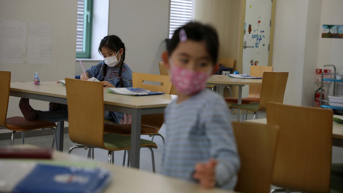 Children, wearing protective face masks, following an outbreak of coronavirus, are seen at Stella Kids, daycare center in Tokyo, Japan, March 5, 2020. REUTERS/Stoyan Nenov