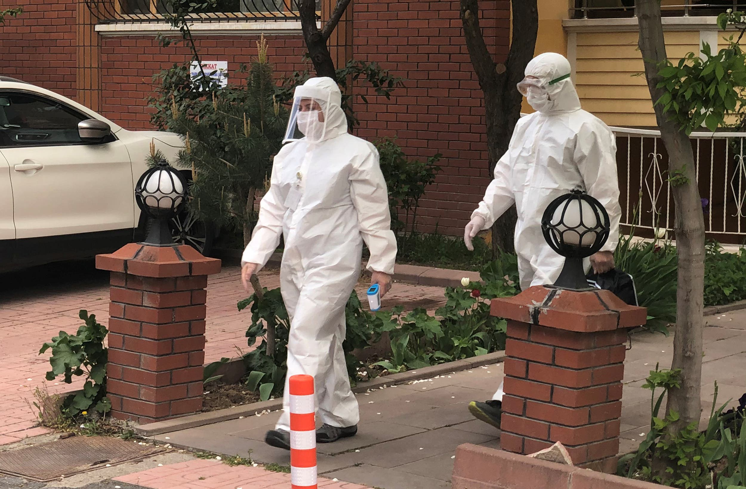 Medics wearing protective suits, members of Turkish Health Ministry's coronavirus contact tracing team, visit a home to check a suspected coronavirus disease (COVID-19) case in Ankara, Turkey, April 27, 2020. (Reuters)