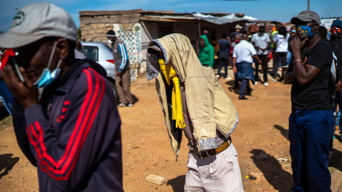 People line up to receive food handouts in the Olievenhoutbos township of Midrand, South Africa on May 2, 2020. (AP)