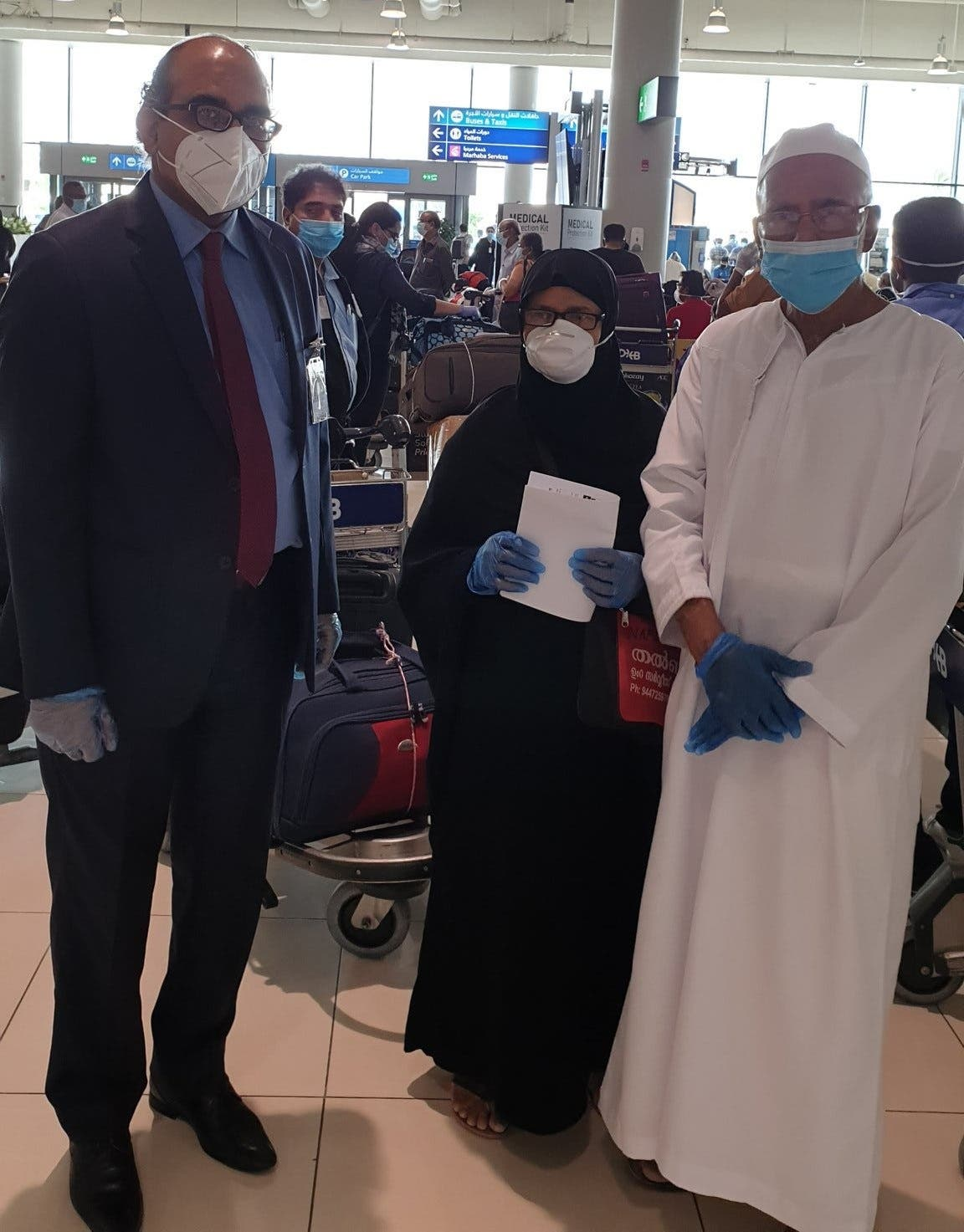 Vipul, the consul general of India in Dubai, with an elderly couple travelling on Dubai-Kozhikode flight at Dubai Airport on Thursday. (Twitter)