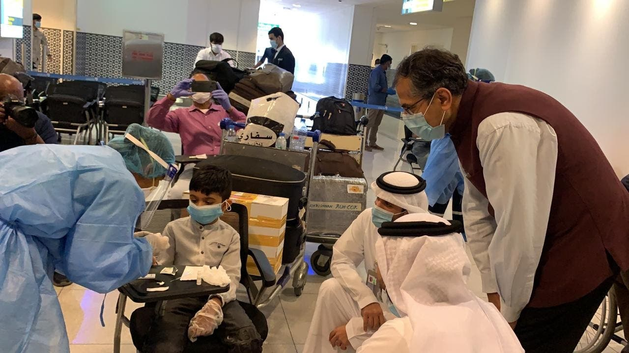 Indian Ambassador to UAE Pavan Kapoor is seen with some of the passengers undergoing medical screening at Abu Dhabi airport before they board the Abu Dhabi-Kochi repatriation flight, on Thursday. (Twitter)