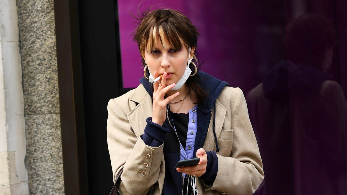 FILE PHOTO: A woman smokes a cigarette while wearing a mask, as the number of coronavirus cases grow around the world, in central London, Britain March 14, 2020. REUTERS/Dylan Martinez/File Photo