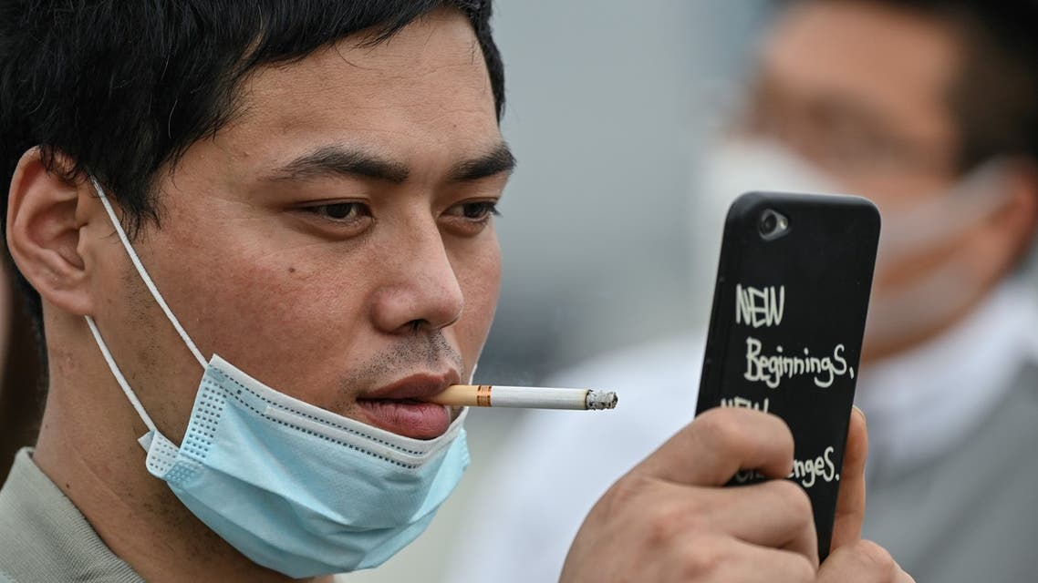 A man smoking a cigarette over a face mask takes a photo at the promenade on the Bund along the Huangpu River during a holiday on May Day, or International Workers' Day, in Shanghai on May 1, 2020. With optimism and a heavy dose of caution, millions of Chinese hit the road or visited newly re-opened tourist sites on May 1 for an extended national holiday in a post-coronavirus confidence test.