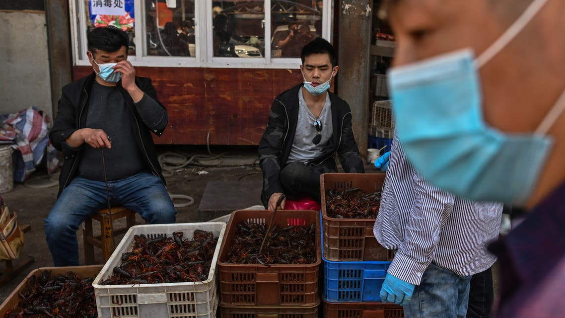 (FILES) In this file photo taken on April 15, 2020, vendors wearing face masks sell prawns at the Wuhan Baishazhou Market in Wuhan in China's central Hubei province. US President Donald Trump's administration is urging an investigation into the origins of the coronavirus pandemic, saying it doesn't rule out that it came from a laboratory researching bats in Wuhan, China. Beijing has said that the virus, which has killed more than 138,700 people worldwide, was likely transmitted to humans late last year at a Wuhan wet market that butchered exotic animals -- a longtime focus of concern for public health experts.