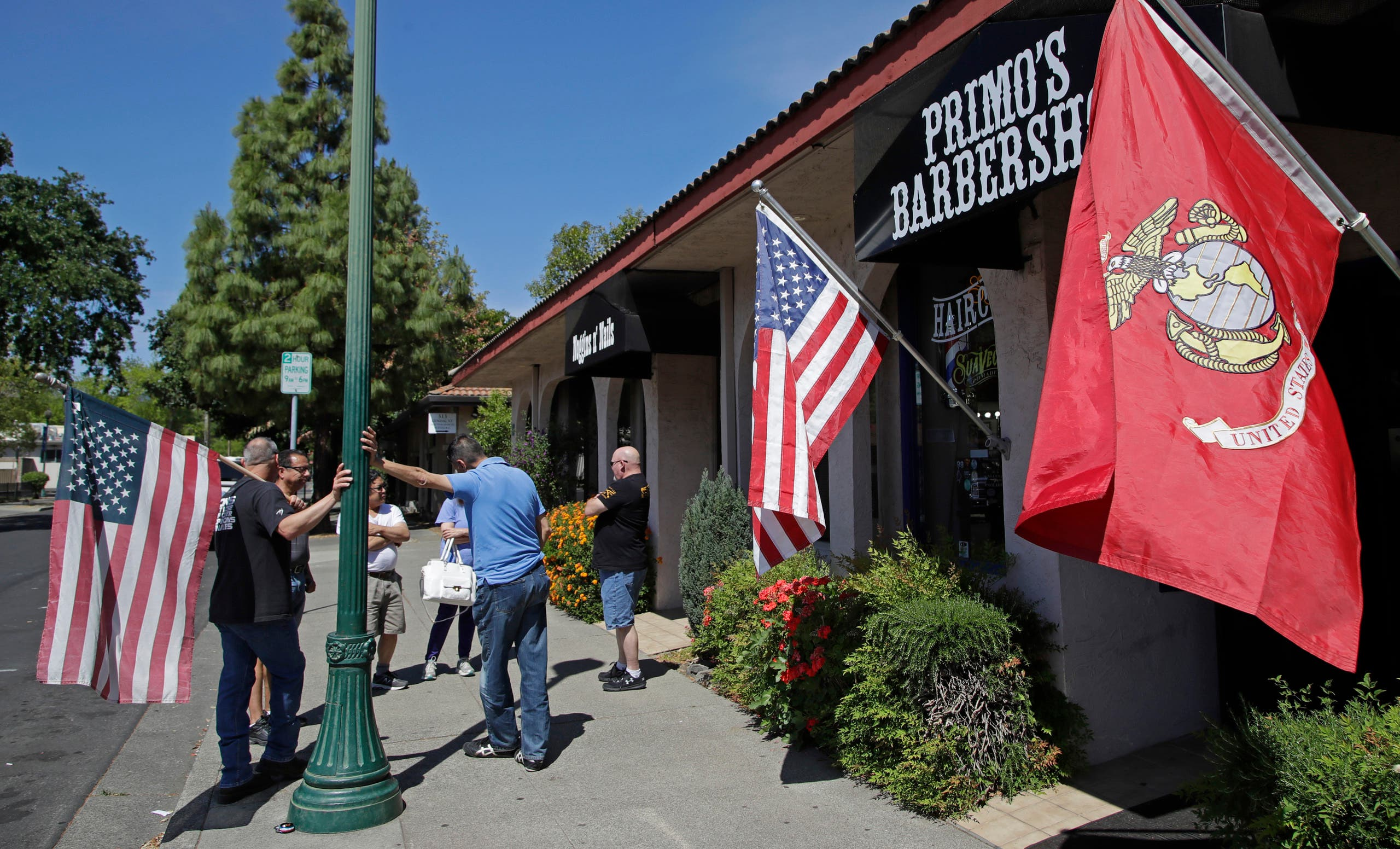 People wait in line to have their hair cut at a barbershop on May 4, 2020, in Vacaville, California. (AP)