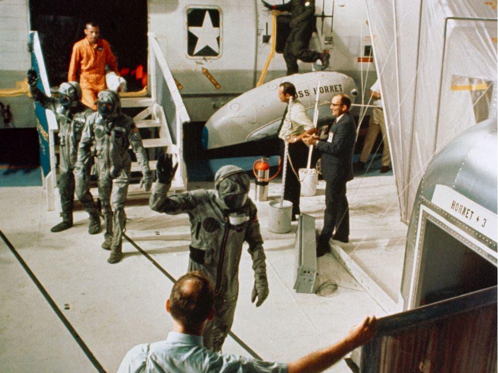 صورة لرواد الفضاء الثلاثة وهم مرتدون لبدلات العزل حال نزولهم