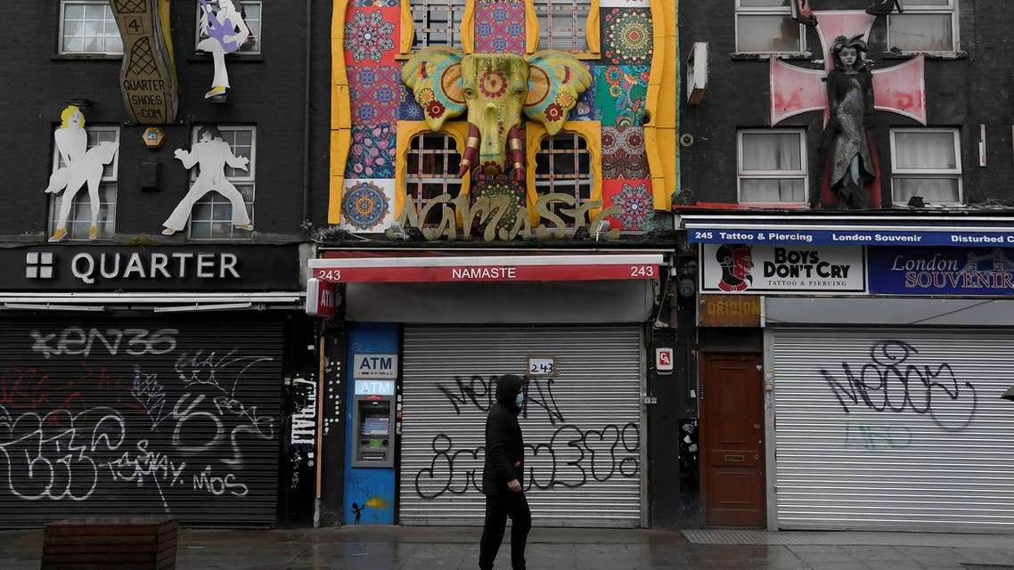 A man wearing a mask walks past closed shops in Camden, following the outbreak of the coronavirus disease (COVID-19), in London, Britain, April 30, 2020. (Reuters)