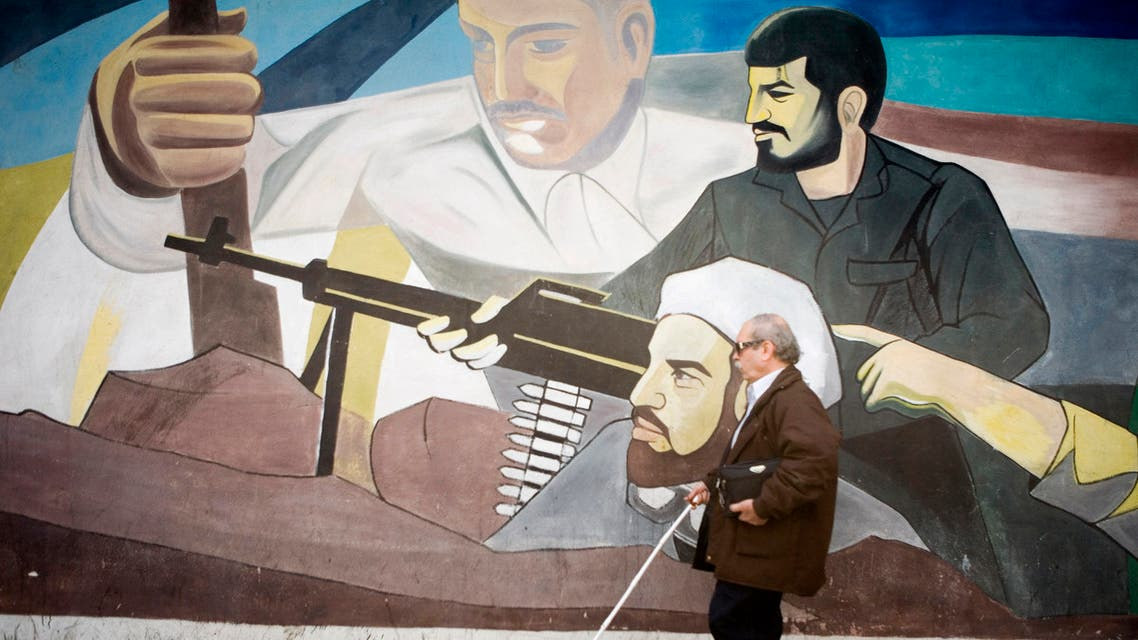 A blind man walks past a mural on a wall at Palestine Square in Tehran March 4, 2007. (Reuters)