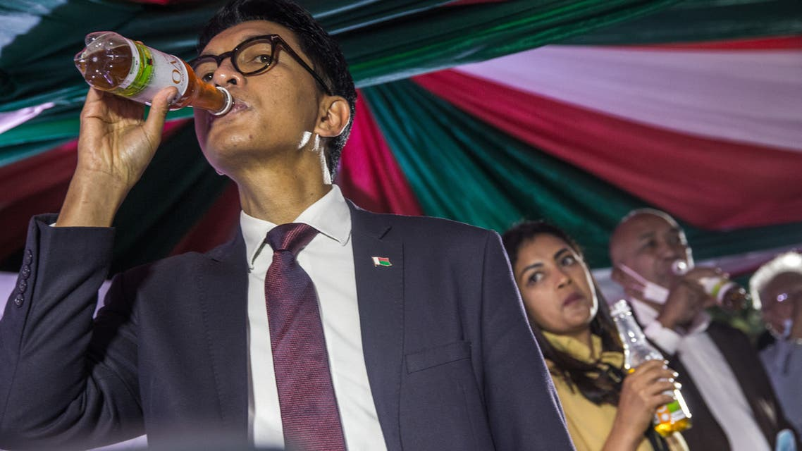 Madagascar's President Andry Rajoelina drinks a sample of the Covid Organics or CVO remedy at a launch ceremony in Antananarivo on April 20, 2020. Covid Organics or CVO is a remedy produced by the Malagasy Institute of Applied Research (IMRA) created from the Artemisia plant and supposedly help to prevent any infection caused by the new coronavirus Covid-19.