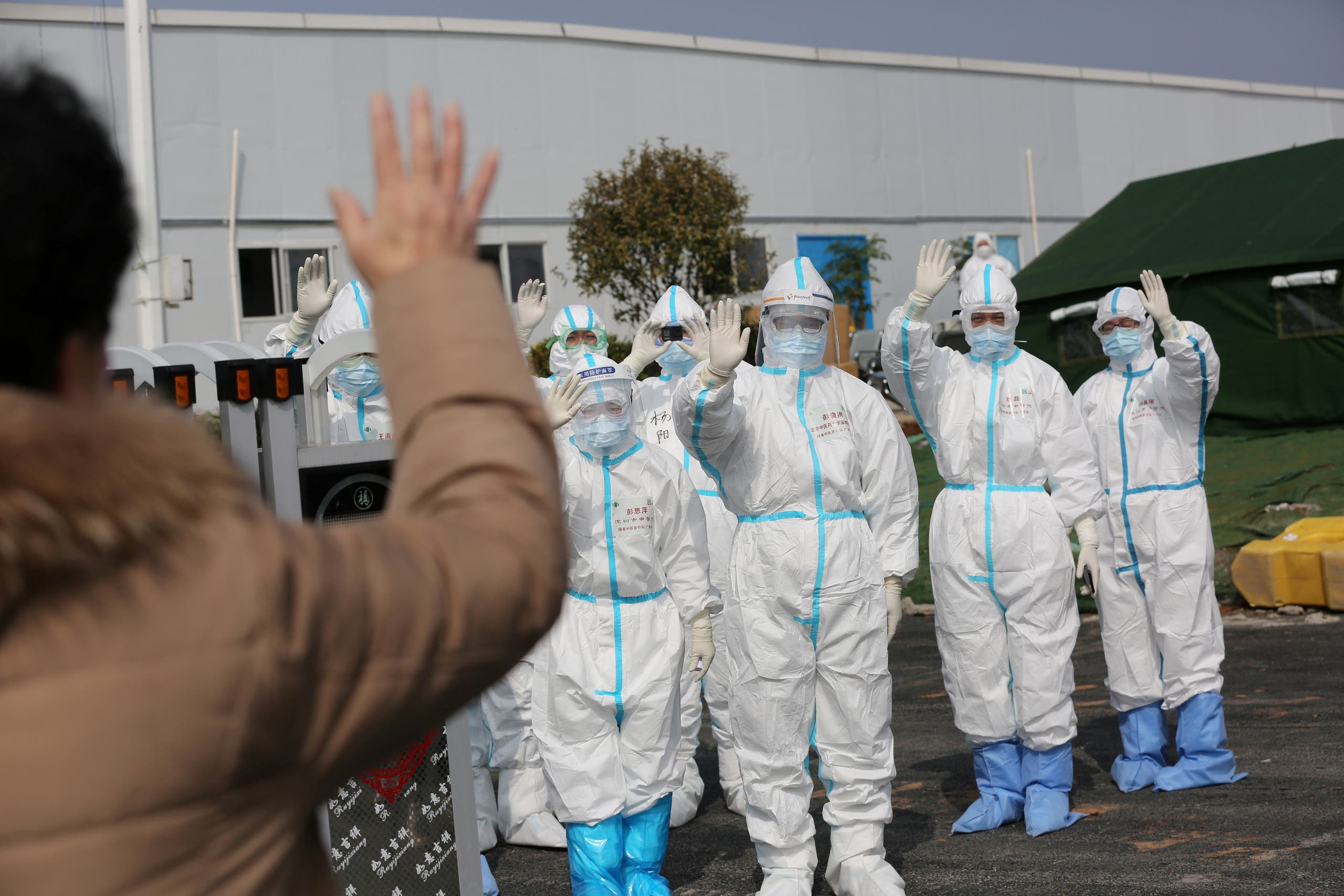 Medical personnel in protective suits wave hands to a patient who is discharged from the Leishenshan Hospital after recovering from the novel coronavirus, in Wuhan, the epicentre of the novel coronavirus outbreak, in Hubei province, China. (File photo: Reuters)