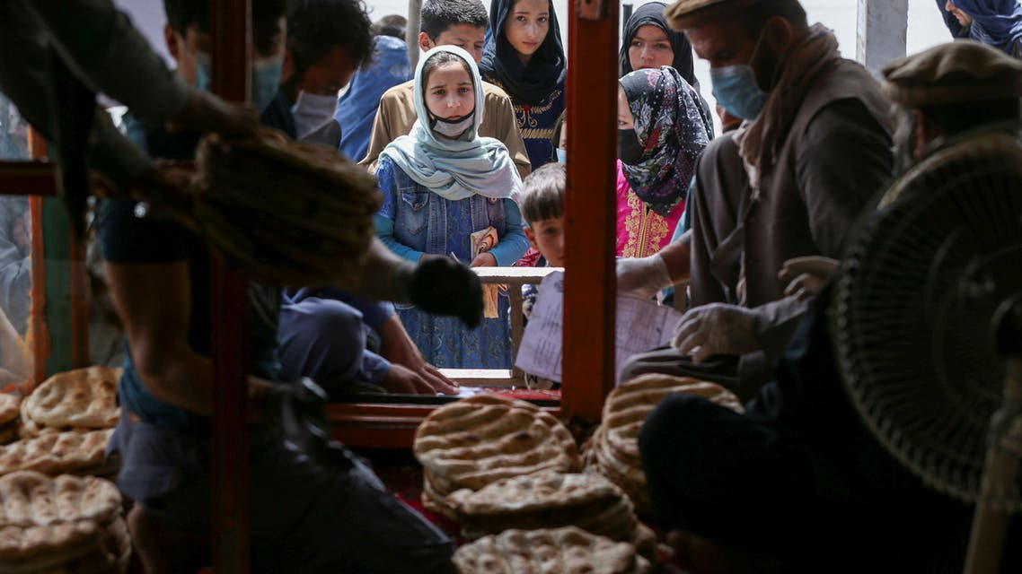 An Afghan family waits for free bread distributed by the government, outside a bakery, during the coronavirus outbreak in Kabul, on May 3, 2020. (Reuters)