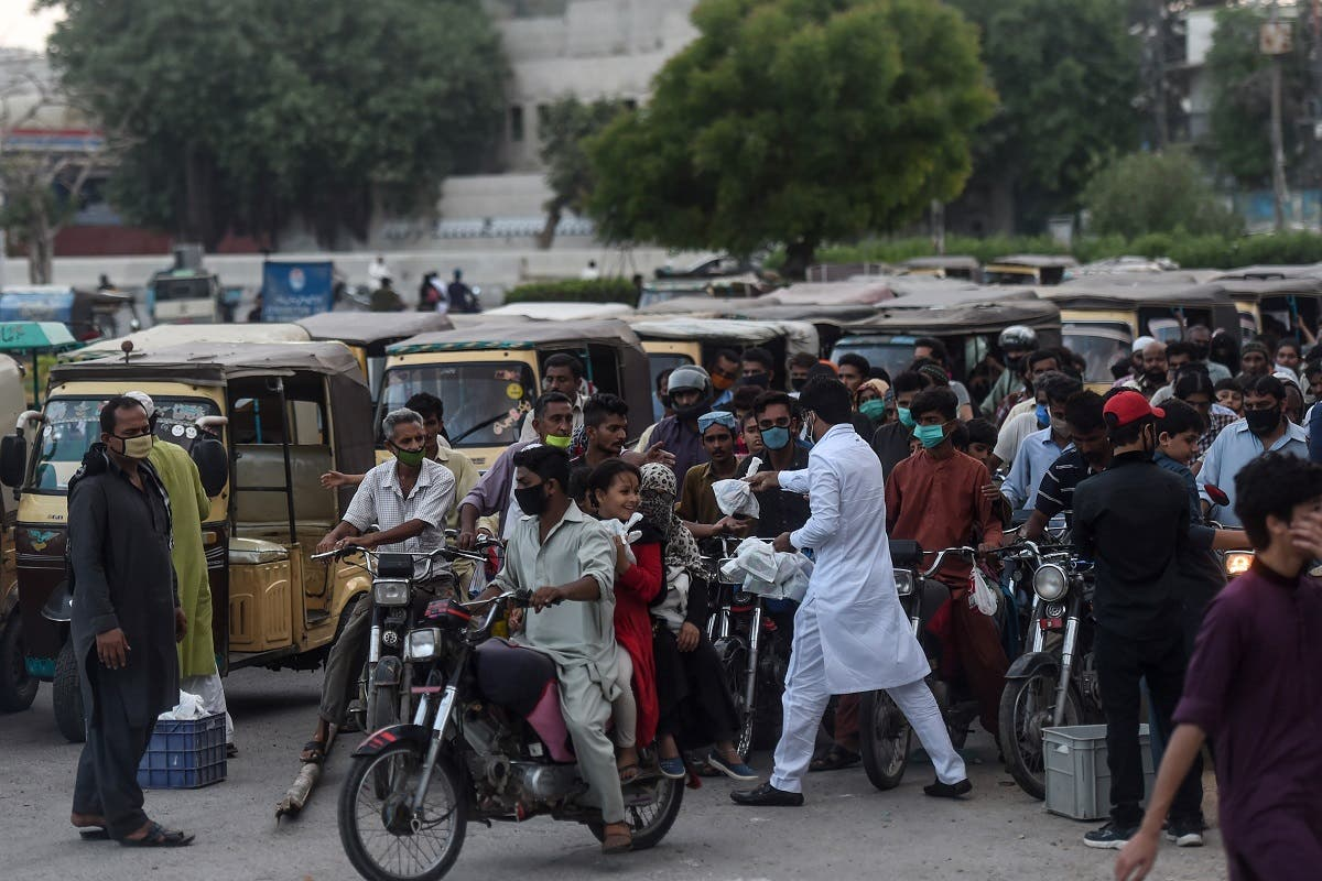 A man (in white) distributes food to people in need during a road traffic after the government eased the nationwide lockdown imposed as a preventive measure against the COVID-19 coronavirus, in Karachi on May 9, 2020. (AFP)