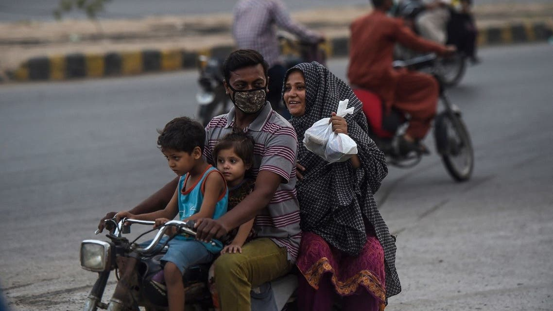 A family riding a motorbike carry food packets distributed by a citizen at a roadside after the government eased the nationwide lockdown imposed as a preventive measure against the COVID-19 coronavirus, in Karachi. (AFP)