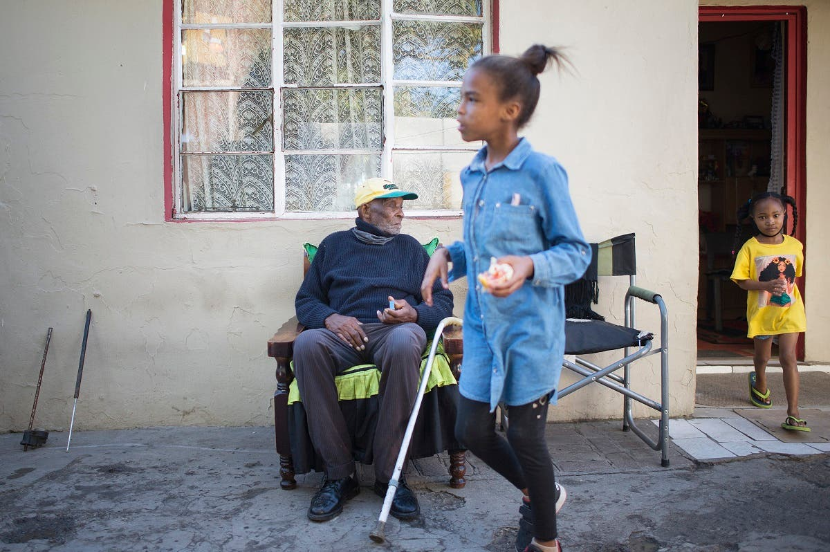 Fredie Blom (L) watches his wife's grandchildren run around as he celebrates his 116th birthday at his home in Delft, near Cape Town, on May 8, 2020. (AFP)