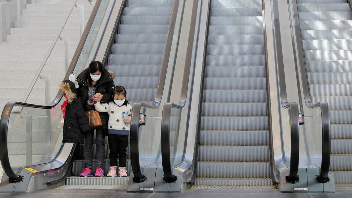 A woman and a child wear masks while on an escalator in John F Kennedy International Airport in New York, U.S., amid coronavirus reports on March 11, 2020. (Reuters)