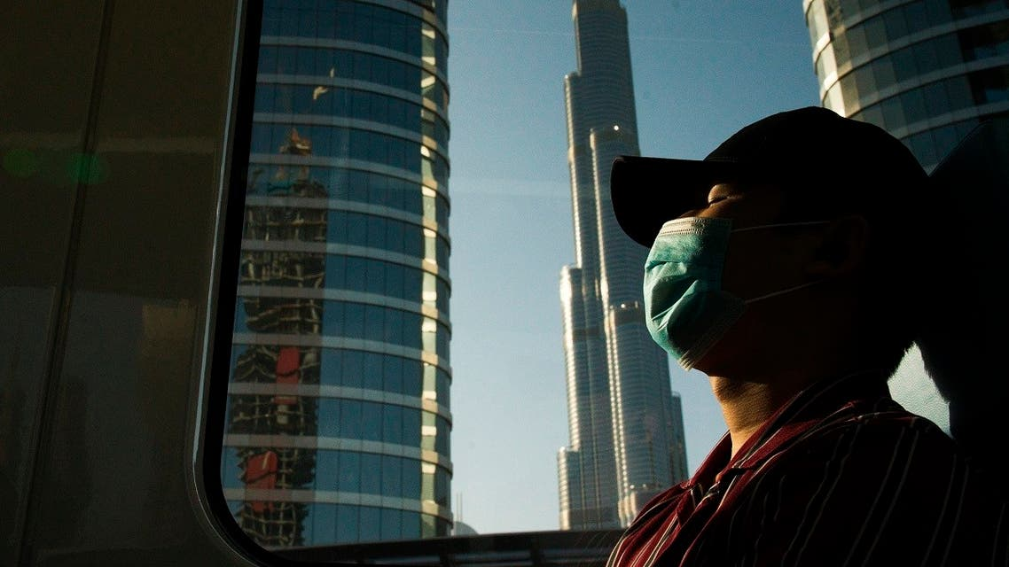 A commuter wearing a face mask to help curb the spread of the coronavirus, sleeps aboard the driverless Metro as it passes the Burj Khalifa, the world's tallest building, in Dubai. (AP)