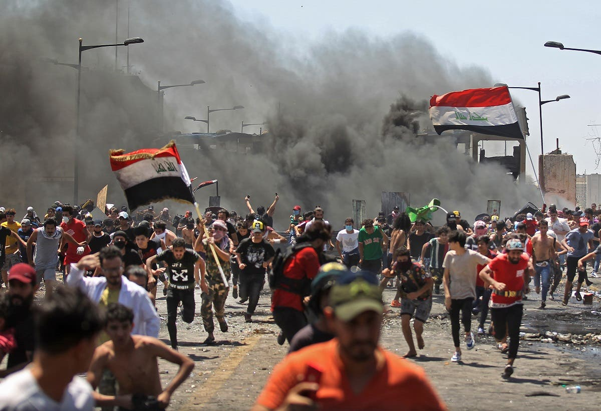Iraqi protesters run for cover as they clash with security forces on Al-Jumhuriyah bridge in the capital Baghdad, during an anti-government demonstration on May 10, 2020. (AFP)