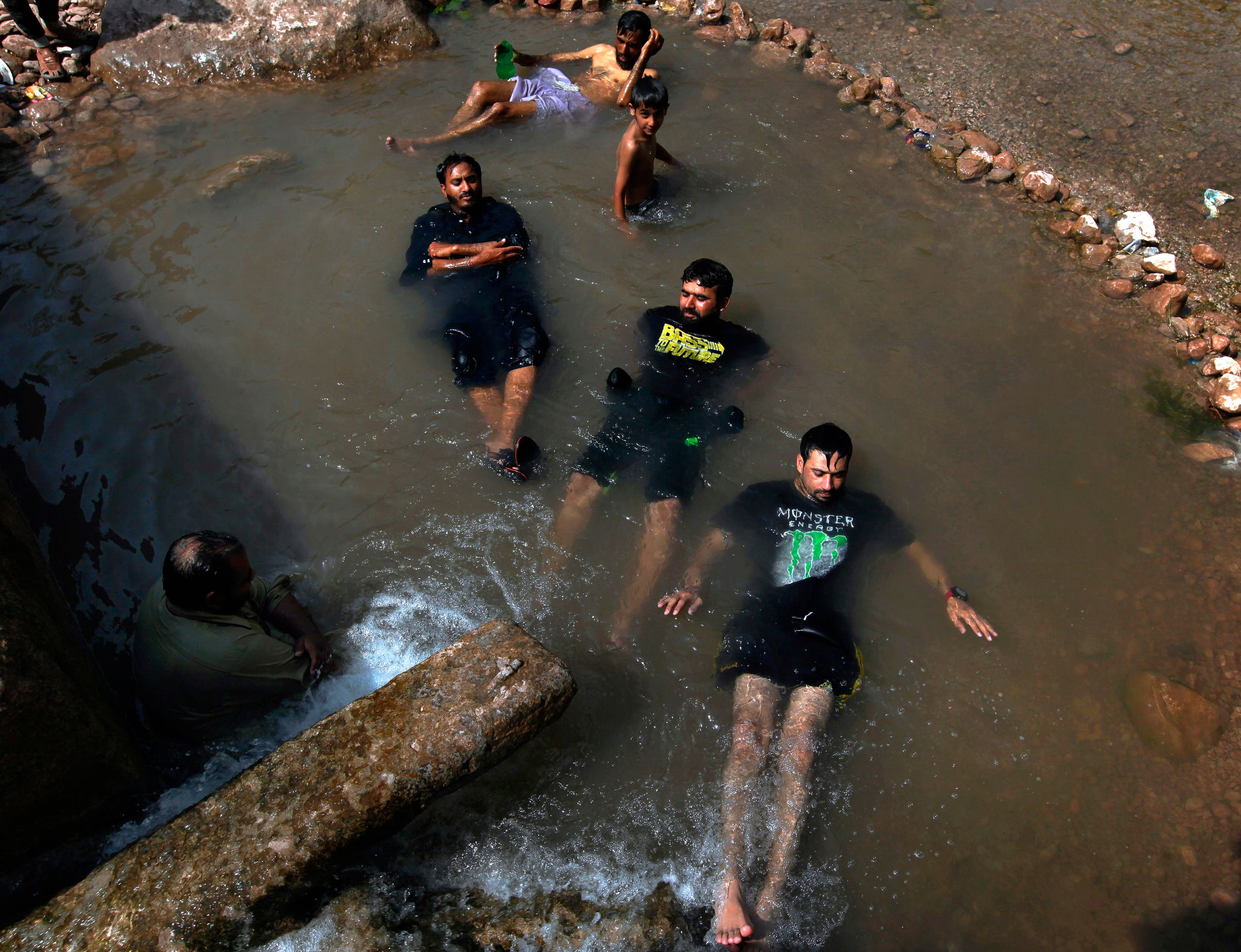 People cool off in a stream during a heat wave, in Islamabad, Pakistan, on June 3, 2018. According to Pakistan's state-run Meteorological Department, many cities are facing heat wave conditions with temperatures reaching 49 C in Sibbi, Moenjodaro, Jacobabad and Bakkar. (AP)