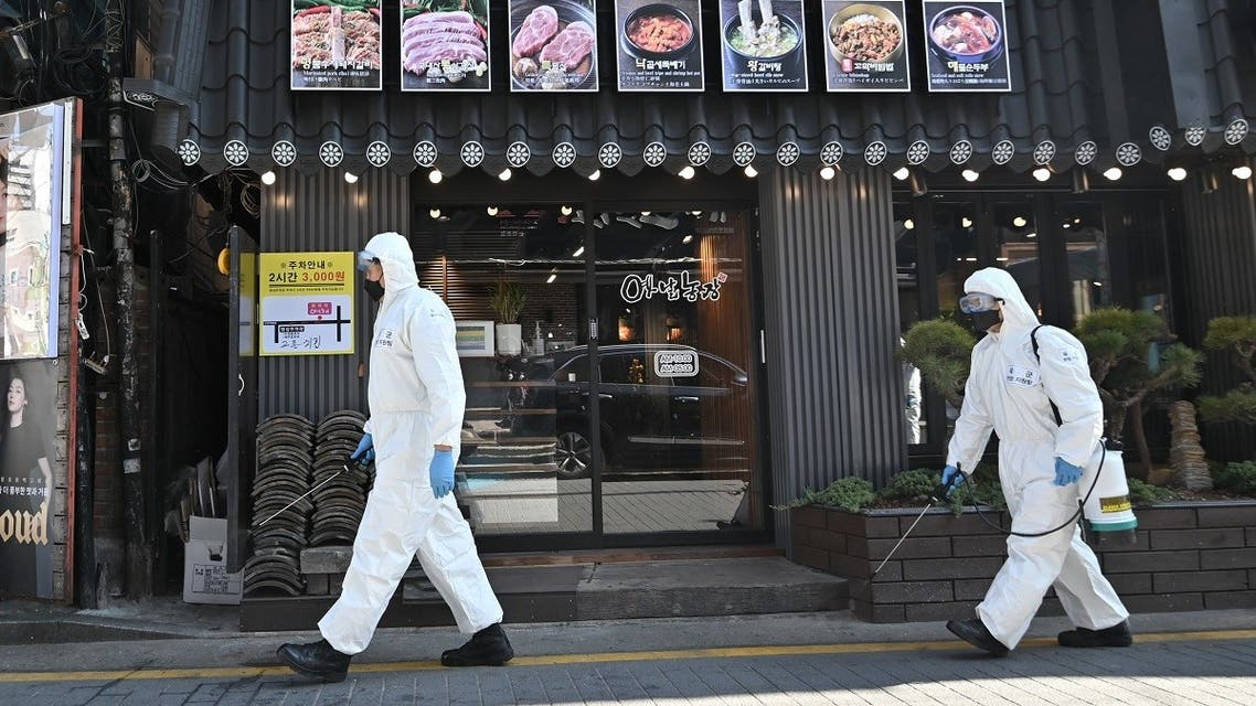 South Korean soldiers wearing protective gear spray disinfectant on the street to help prevent the spread of the COVID-19 coronavirus, at Gangnam district in Seoul. (AFP)