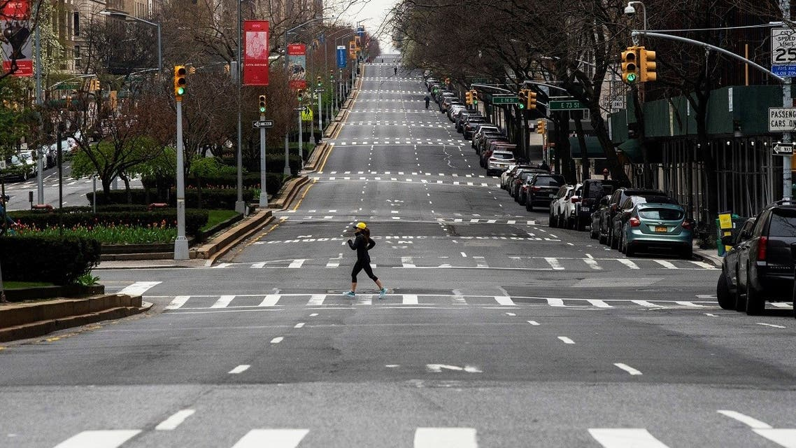 A woman crosses the empty of street Park Avenue in Manhattan as the outbreak of coronavirus disease (COVID-19) continues in New York. (AFP)