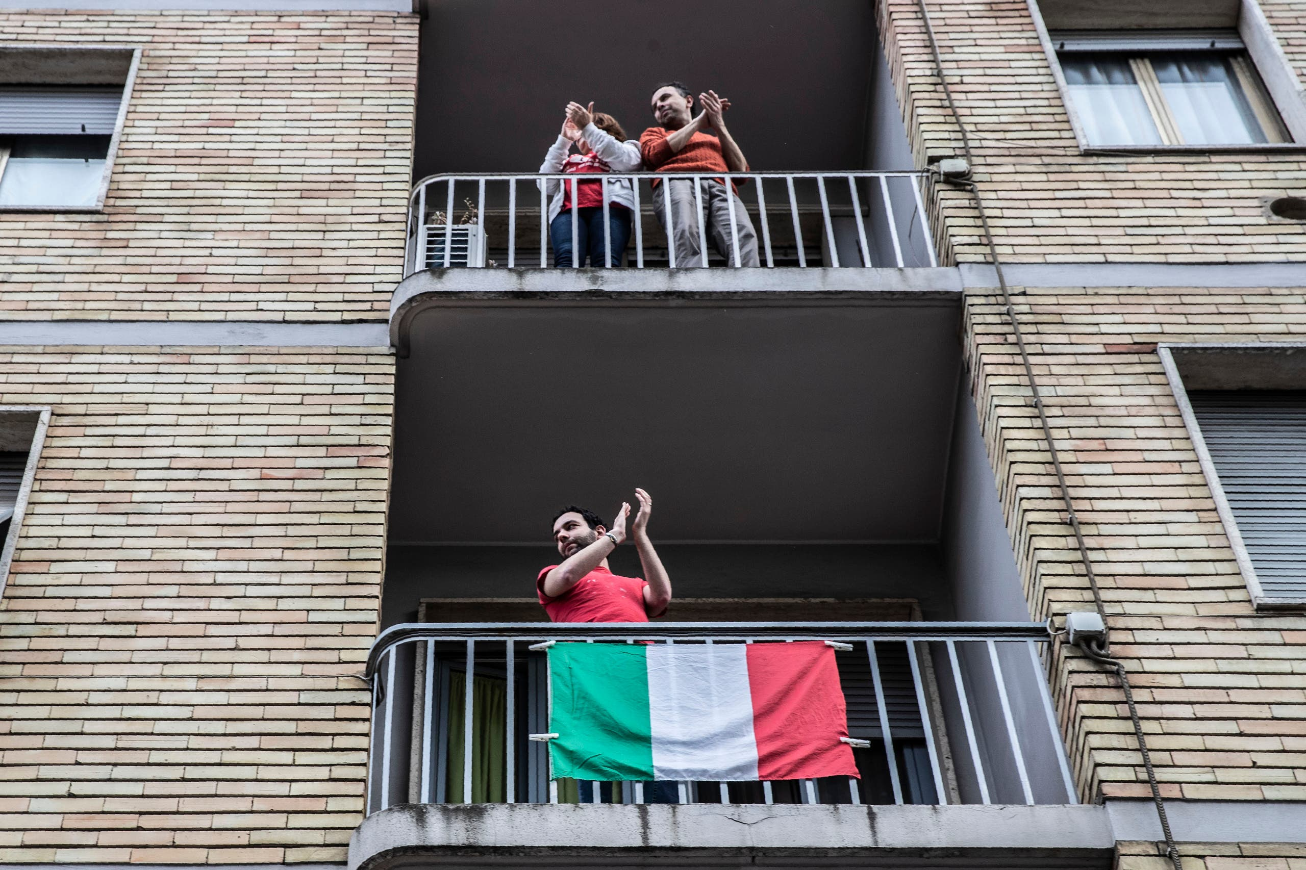 People applaud from balconies in front of the house of 23-year-old Italian volunteer Silvia Costanza Romano, in Milan, Italy on May, 10, 2020. (AP)