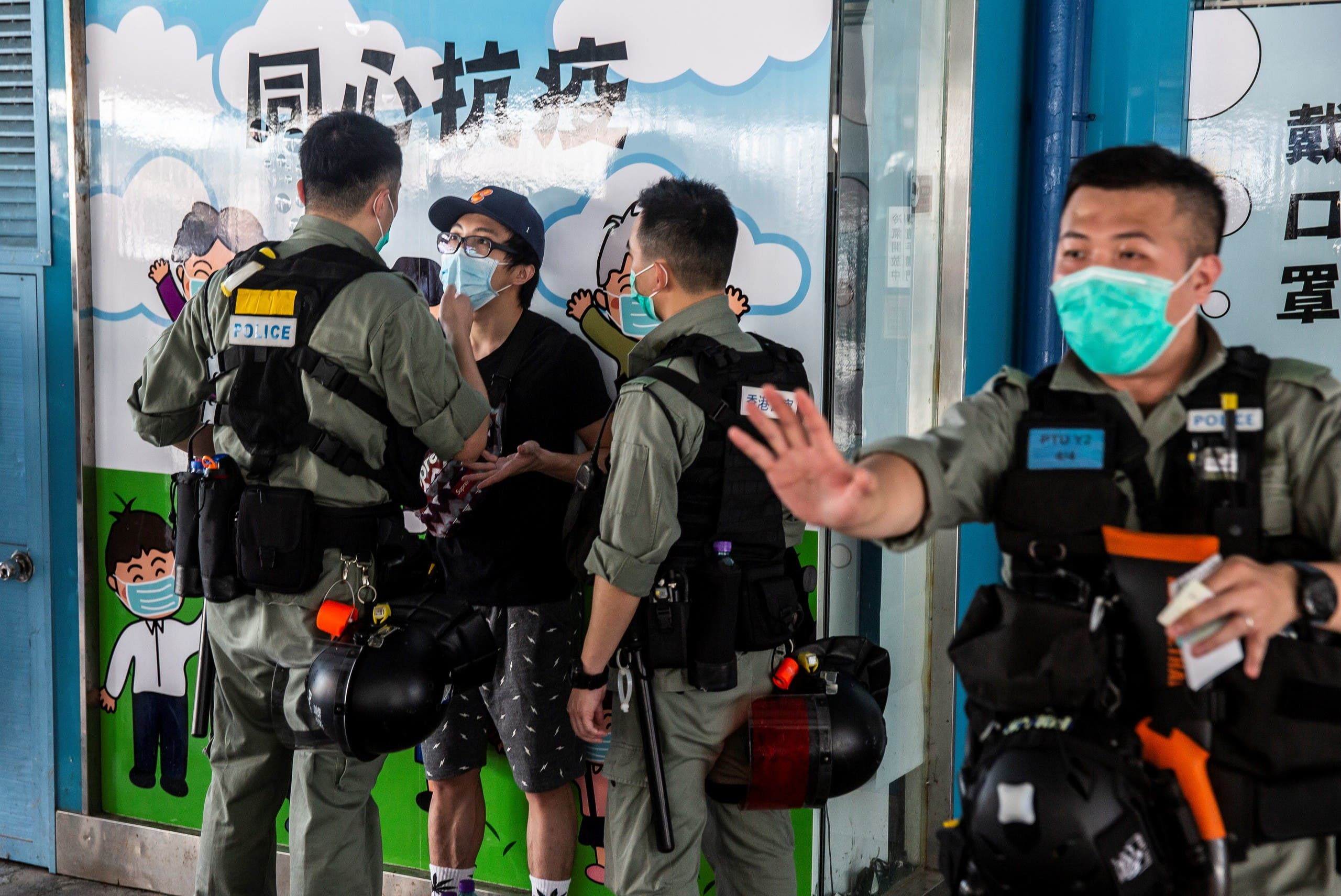 Police officers talk to a man as they patrol in Hong Kong on May 10, 2020. (AFP)