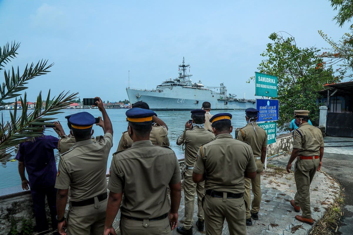 Kerala police personnel watch and take photos as the INS Jalashwa ship enters the Cochin port carrying Indian citizens who were stranded in Maldives, in Kochi in the south Indian state of Kerala on May 10, 2020. (AFP)