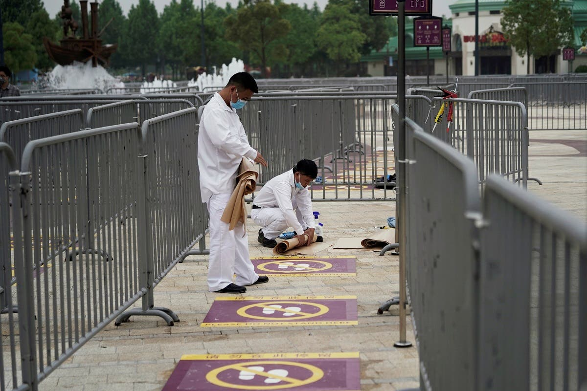 Workers wearing face masks prepare social distancing markers at Shanghai Disney Resort. (Reuters)