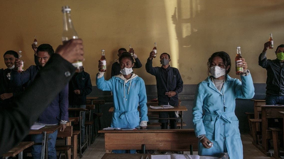 Students hold up bottles of Covid Organics that the authorities gave each student and encouraged them to drink it before the start of classes at the J.J. Rabearivelo High School in downtown Antananarivo on April 23 2020. (AFP)