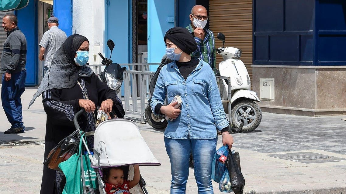Tunisians wearing protective masks walk in the Kram area of the capital Tunis on May 8, 2020, as authorities begin a gradual sector and region-based process to mitigate lockdown measures. (AFP)