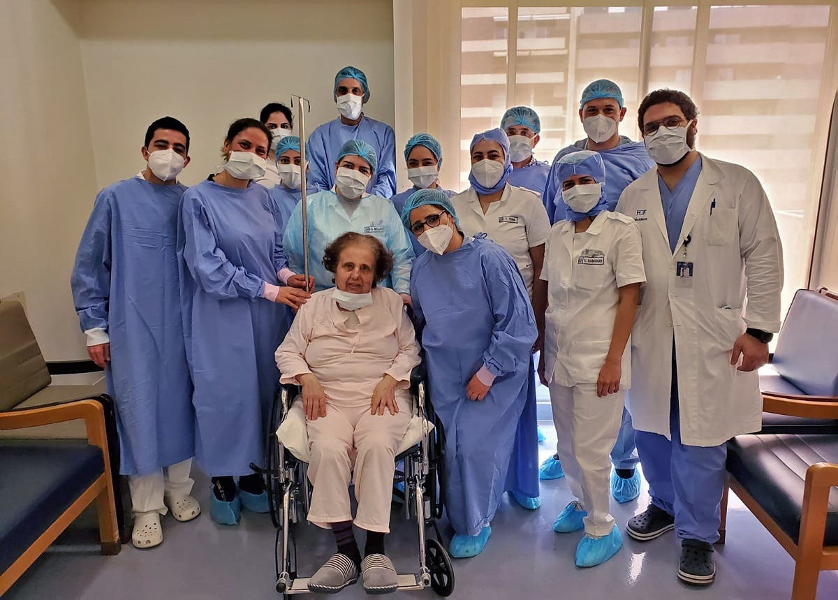 A picture taken by a nurse on April 30, 2020 at the Hotel Dieu de France Hospital, shows colleagues surrounding a patient as they pose for a souvenir photograph in the coronavirus COVID-19 section of the hospital. (AFP)
