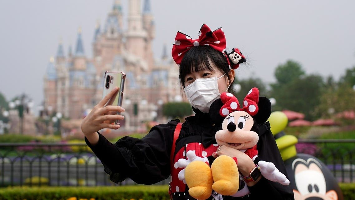 A visitor dressed as a Disney character takes a selfie while wearing a protective face mask at Shanghai Disney Resort as the Shanghai Disneyland theme park reopens following a shutdown due to the coronavirus disease (COVID-19) outbreak, in Shanghai, China May 11, 2020. (Reuters)