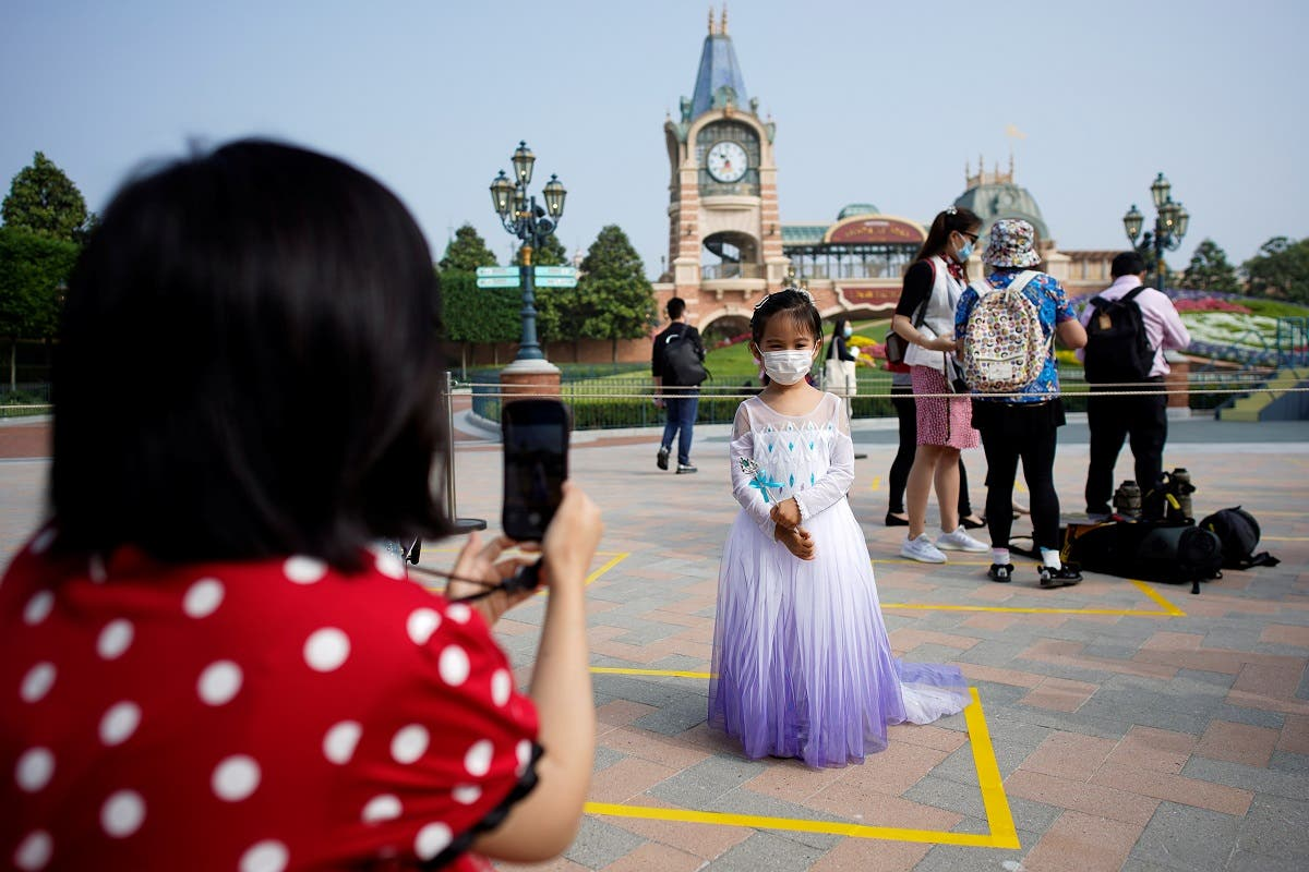 A girl wearing face mask poses for a picture at Shanghai Disney Resort as the Shanghai Disneyland theme park reopens following a shutdown due to the coronavirus disease (COVID-19) outbreak, in Shanghai, China May 11, 2020. (Reuters)