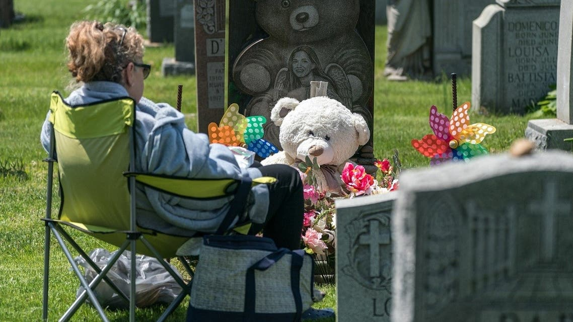 A woman visits her daughter's grave at Calvary Cemetery on May 10, 2020 in the Queens borough of New York City. (AFP)