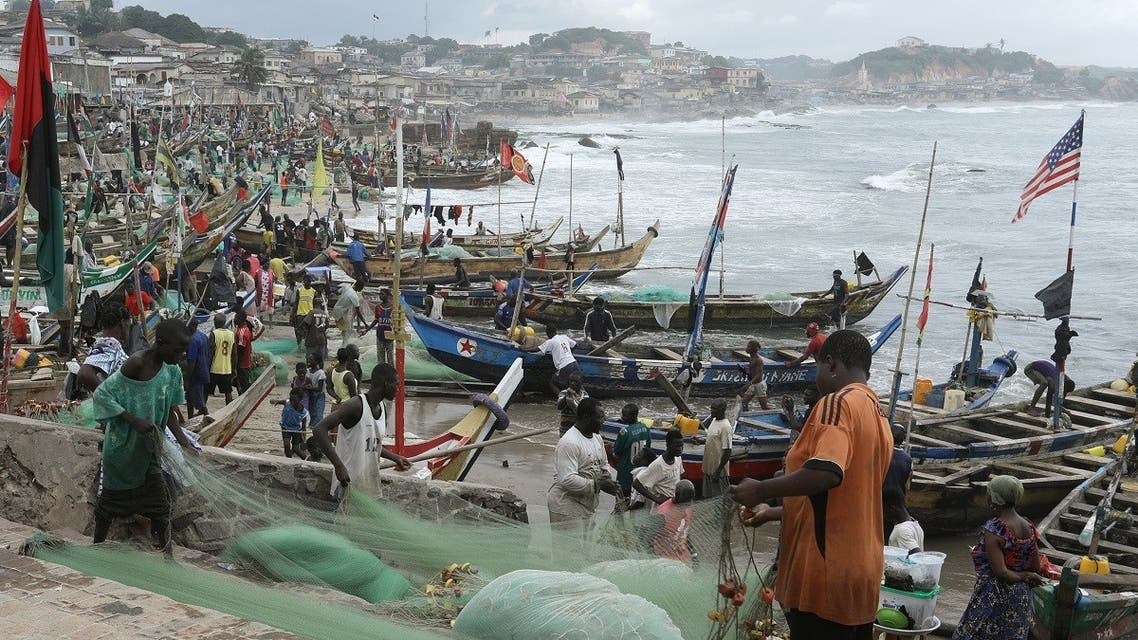 Fishermen tend their boats and fishing nets as members of a heritage tour group, traveling to Ghana to discover their roots, visit the Cape Coast castle, Ghana August 12, 2019. Picture taken August 12, 2019. (Reuters)