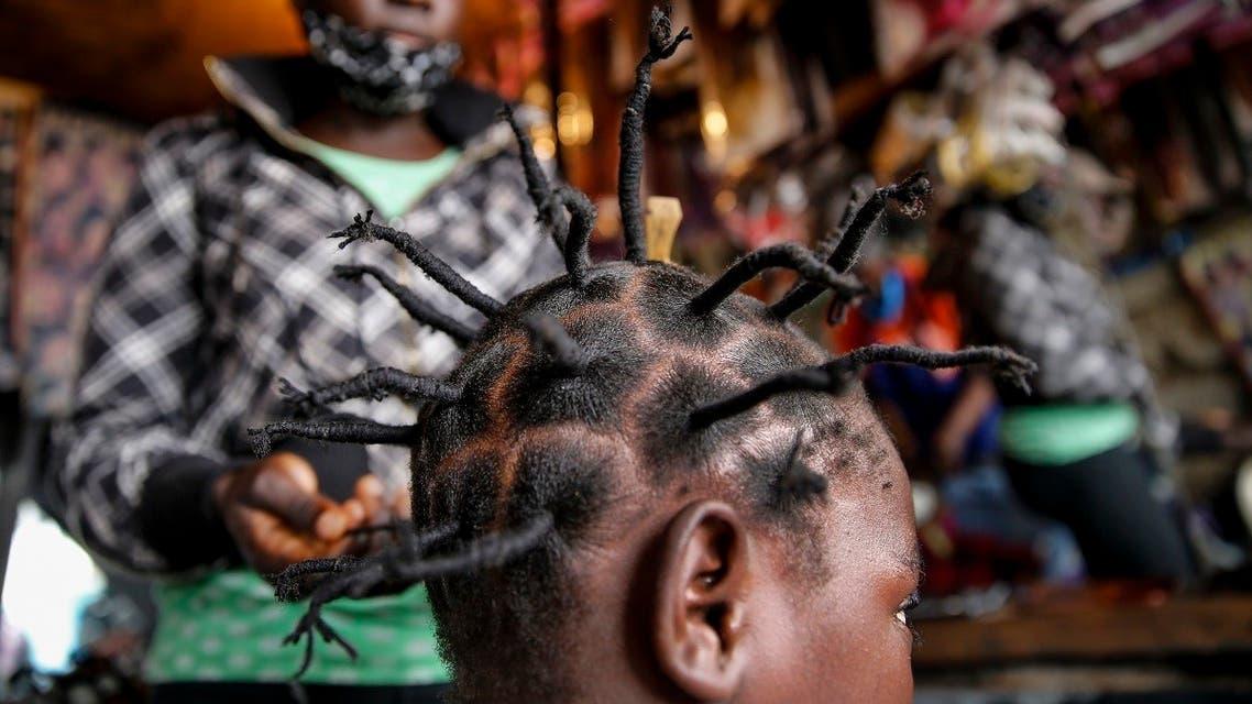 Gettrueth Ambio, 12, has her hair styled in the shape of the new coronavirus, at the Mama Brayo Beauty Salon in the Kibera slum, or informal settlement, of Nairobi, Kenya. (AP)