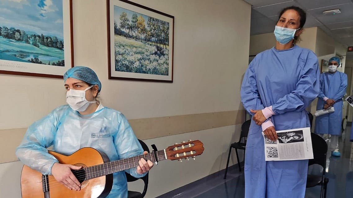 A picture taken by a nurse on May 8, 2020 at the Hotel Dieu de France Hospital, shows a colleague entertaining others with a guitar during a break in the coronavirus section of the hospital in Beirut's eastern suburbs. (AFP)