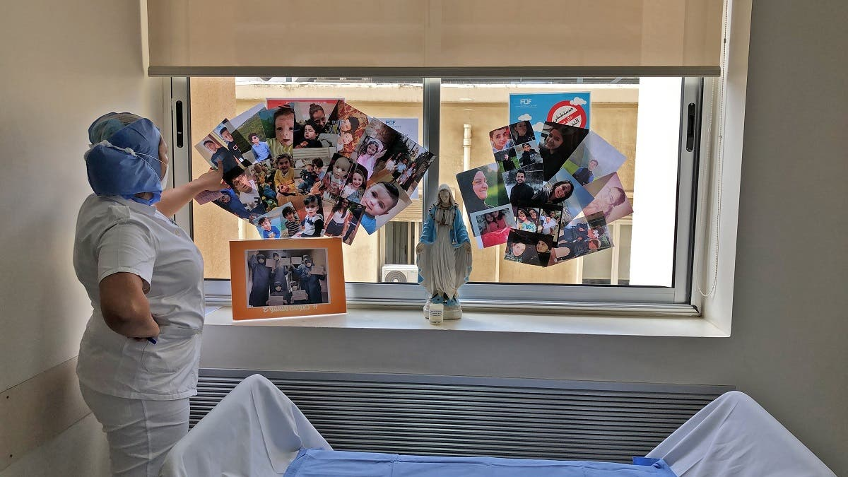 A picture taken by a nurse on April 30, 2020 at the Hotel Dieu de France Hospital, shows a colleague staring at family pictures displayed on a window behind a statue of the Virgin Mary in the coronavirus section of the hospital. (AFP)