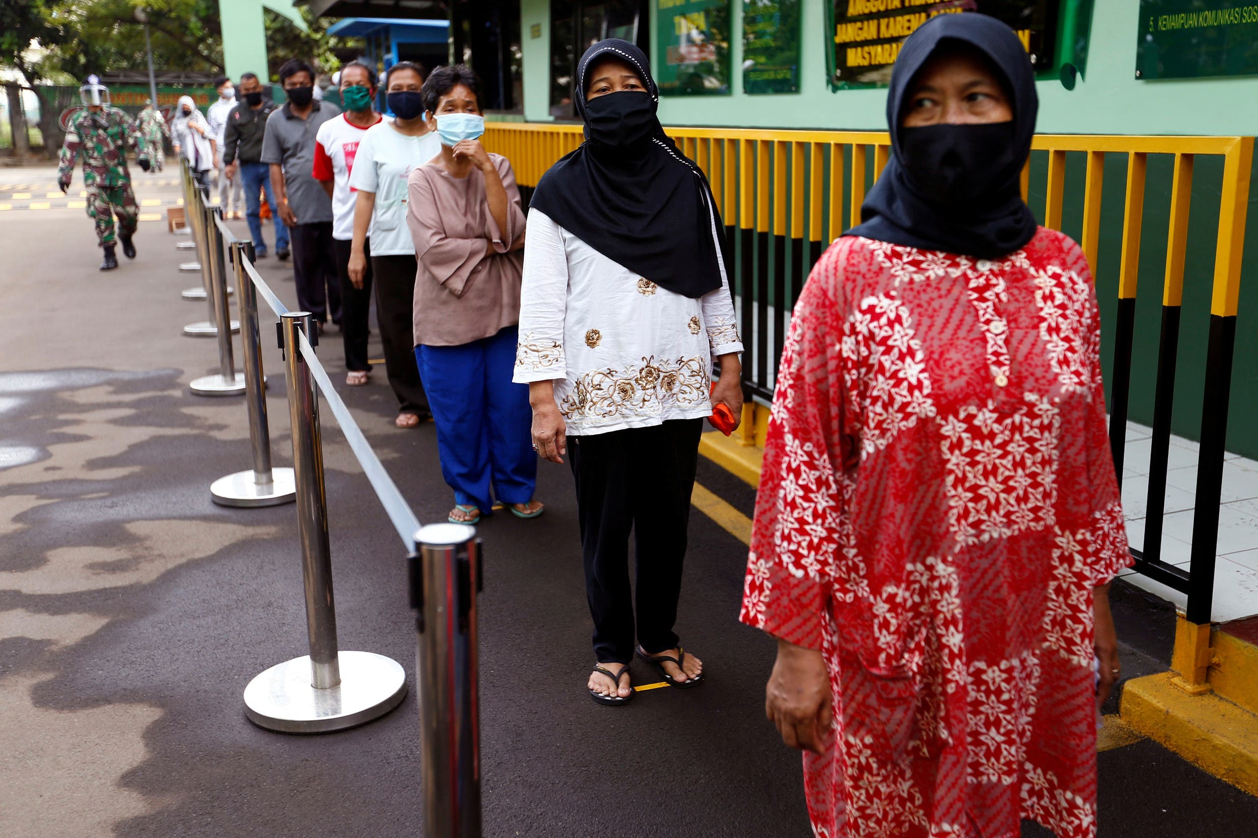 People wearing protective face mask practice social distancing while receiving rice from an automated rice ATM distributor amid the spread of the coronavirus disease (COVID-19) in Jakarta, Indonesia, May 4, 2020. (Reuters)