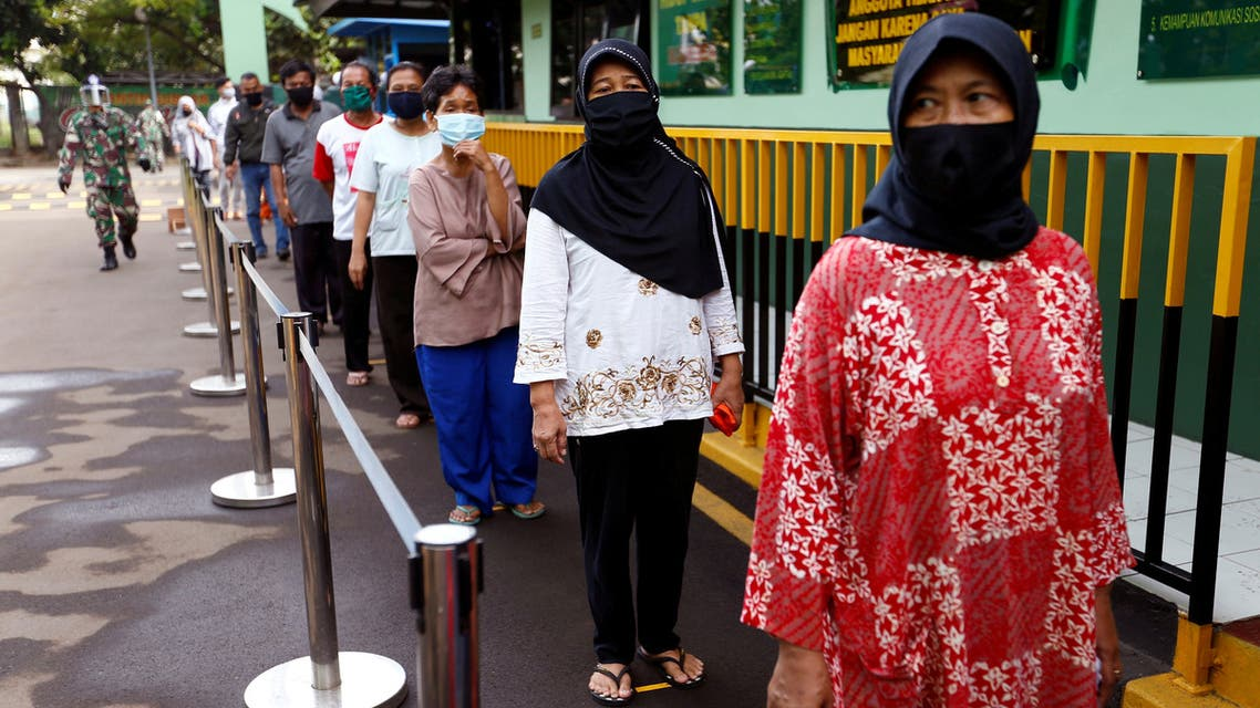FILE PHOTO: People wearing protective face mask practice social distancing while receiving rice from an automated rice ATM distributor amid the spread of the coronavirus disease (COVID-19) in Jakarta, Indonesia, May 4, 2020. REUTERS/Ajeng Dinar Ulfiana/File Photo