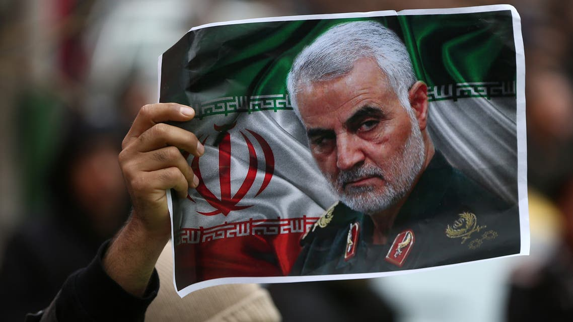 An Iranian holds a picture of late General Qassem Soleimani, head of the elite Quds Force, who was killed in an air strike at Baghdad airport, as people gather to mourn him in Tehran, Iran January 4, 2020. (Reuters)