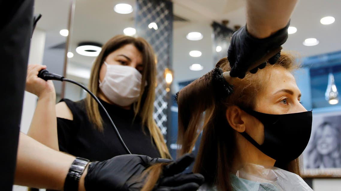 A hairdresser gives hair treatment to his customer Elena Kuznetsova, wearing a protective mask, on the first day of the reopening of his hair salon which was closed since March 21 amid the spread of the coronavirus disease (COVID-19), in Istanbul, Turkey, May 11, 2020. REUTERS/Umit Bektas