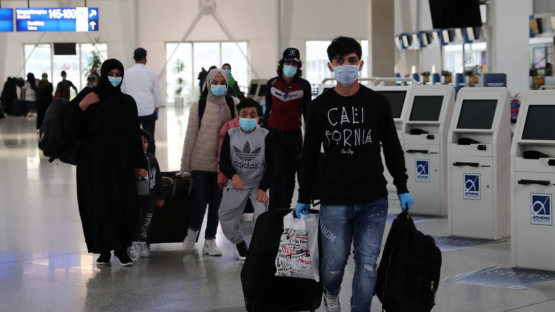Refugees and migrants from overcrowded migrant camps who will be transferred to Britain where they will reunite with their families, wear protective face masks as a precaution against the coronavirus disease (COVID-19) at the check-in area at the Athens International Airport, Greece, May 11, 2020. REUTERS/Alkis Konstantinidis