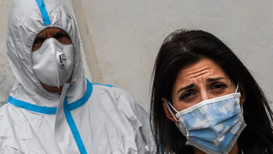 Rome mayor Virginia Raggi, wearing a face mask (R) and an employee of Rome's Municipal Environment Company (AMA), wearing protective overall and mask, attend the sanitation of the Santuario della Madonna del Divino Amore church on May 13, 2020 in the southern Castel di Leva district of Rome, during the country's lockdown aimed at curbing the spread of the infection caused by the novel coronavirus. The Italian Army, at the specific request of the Vicariate of Rome, started on May 13, 2020 the sanitation of Rome's churches through its specialized teams in the Chemical, Biological, Radiological and Nuclear (CBRN) fields. The activity, in collaboration with the municipality of Rome, will proceed according to a specific calendar for blocks of municipalities and provide for the sanitation of over 337 parish churches.