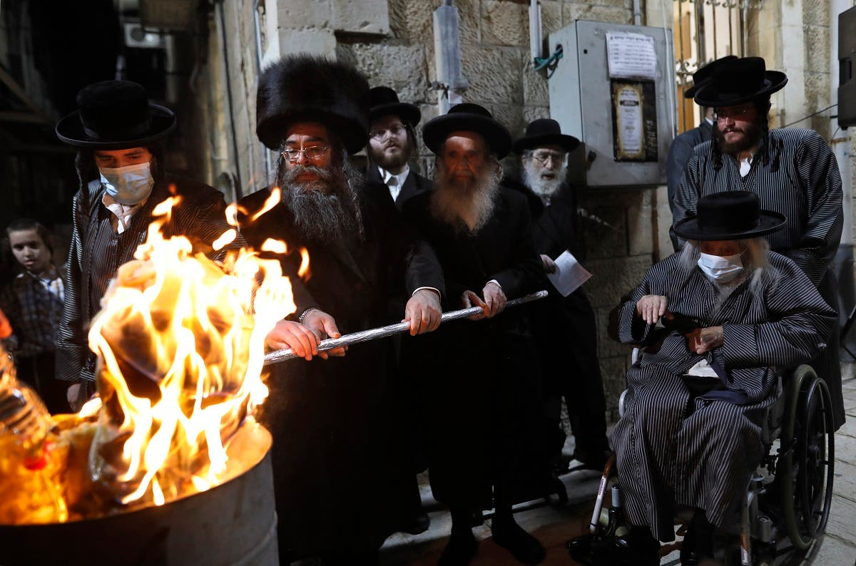 Ultra-Orthodox Jews light a Lag BaOmer bonfire in Jerusalem's religious Mea Shearim neighborhood amid orders to cancel all Lag BaOmer holiday celebrations, on May 11, 2020, during the coronavirus pandemic. (AFP)