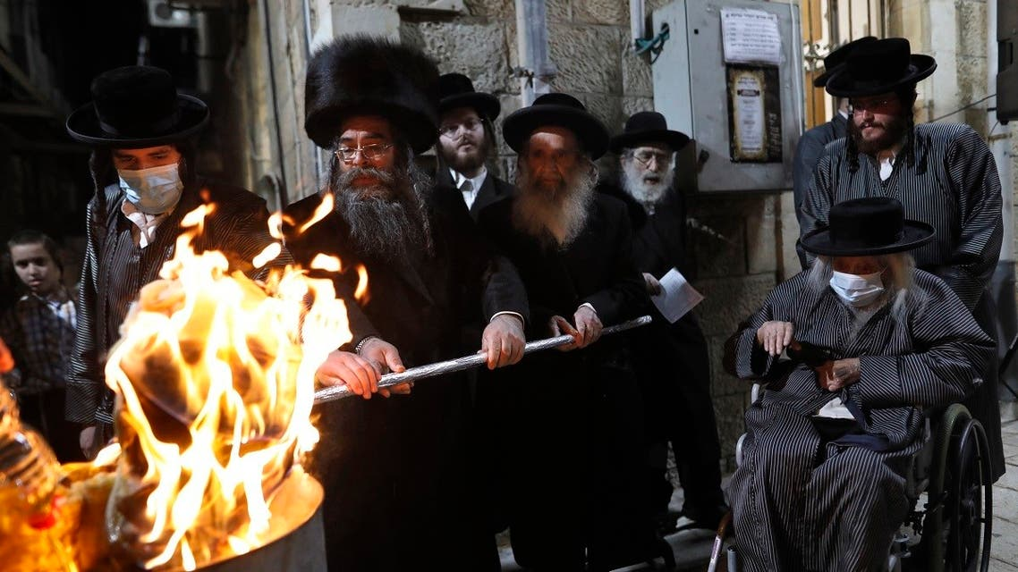 Ultra-Orthodox Jews light a Lag BaOmer bonfire in Jerusalem's religious Mea Shearim neighbourhood amid an Israeli health ministry's order to maintain social distancing and to cancel all Lag BaOmer holiday celebrations, on May 11, 2020, during the COVID-19 coronavirus pandemic. (AFP)