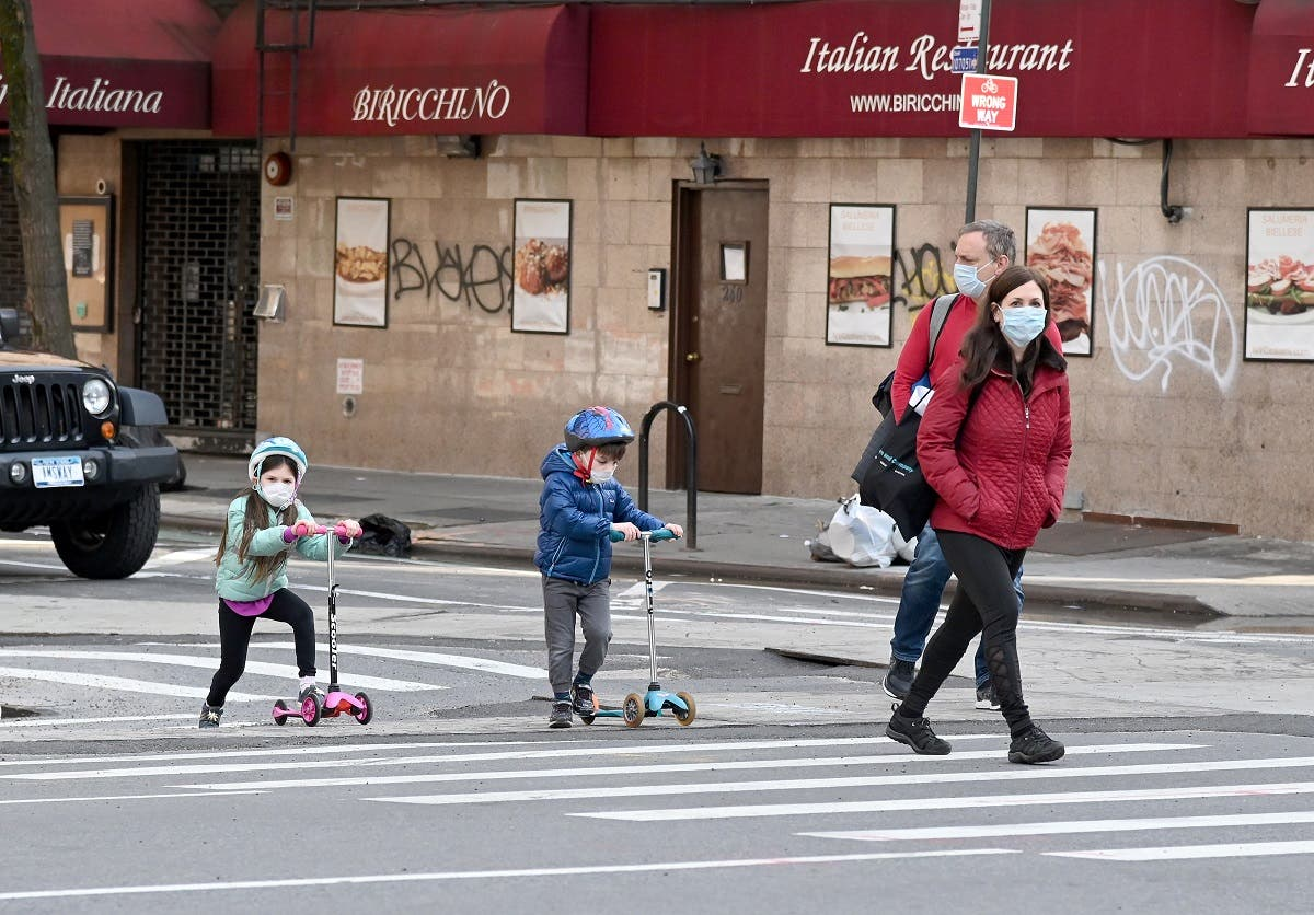 Children wearing face masks play on their scooters while their parents watch during the coronavirus pandemic on April 25, 2020 in New York City. (AFP)