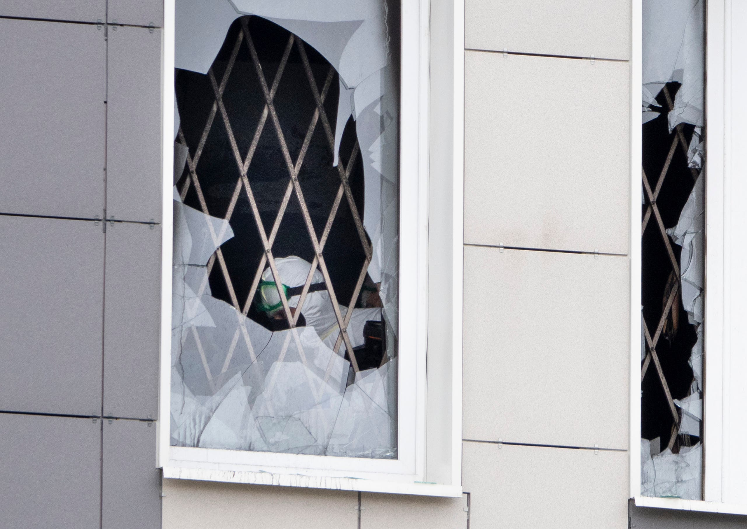 An investigator is seen through a broken window at the scene of a fire at St. George Hospital in St. Petersburg, Russia. (AP)