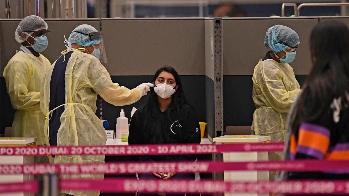Health workers check passengers who arrived in an Emirates Airlines flight from London at Dubai International Airport on May 8, 2020 amid the coronavirus Covid-19 pandemic. (AFP)