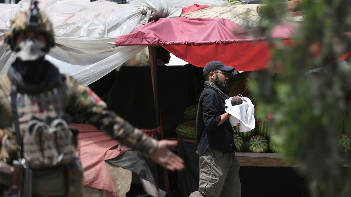 An Afghan security officer carries a baby after gunmen attacked a maternity hospital, in Kabul, Afghanistan on May 12, 2020. (AP)